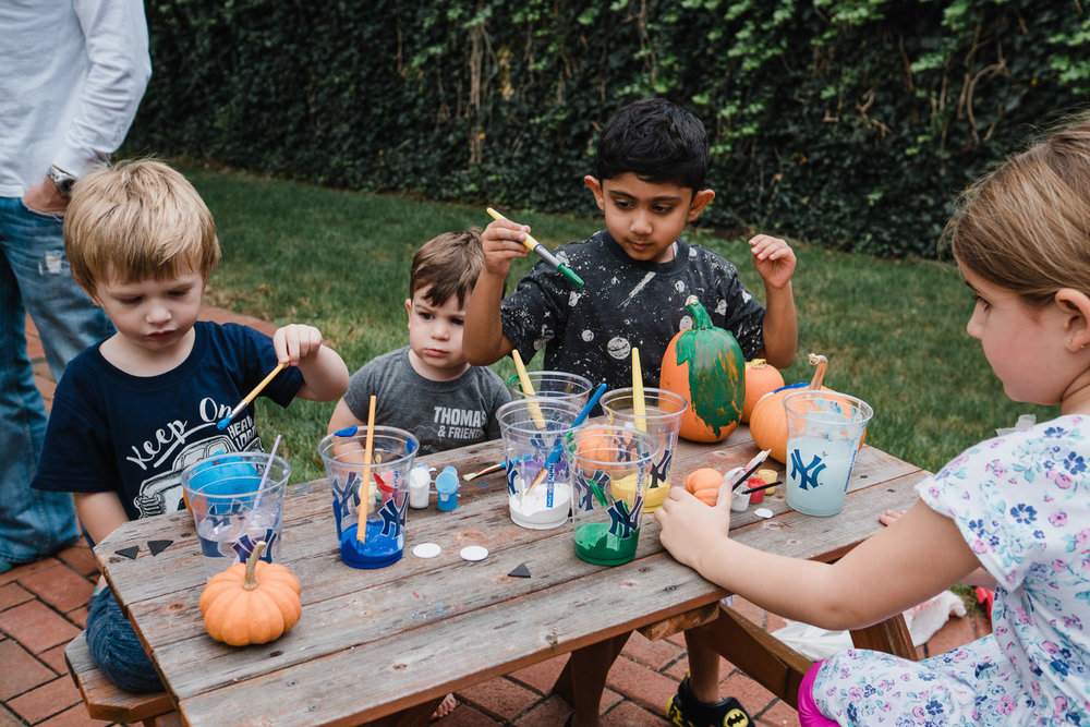 Children paint pumpkins.