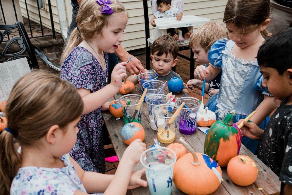 Children paint pumpkins outside.