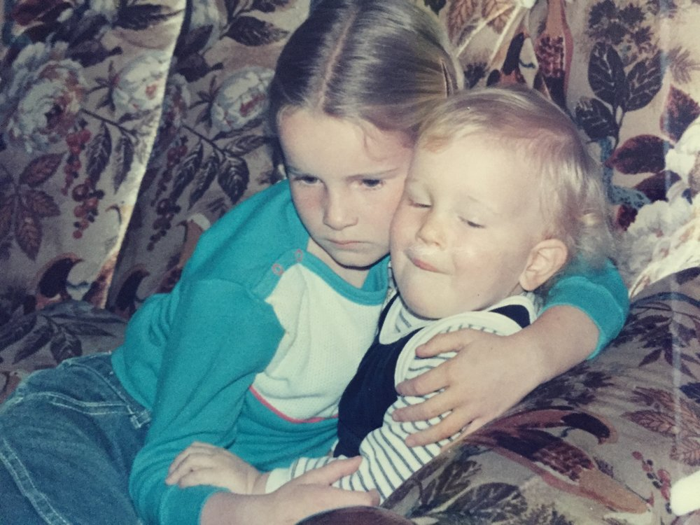 Two young children embrace on a couch.