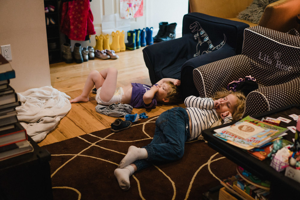 Two kids lay around on the floor and watch TV.