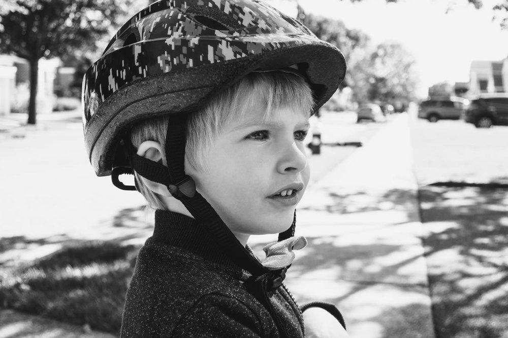 A portrait of a little boy in a bike helmet.
