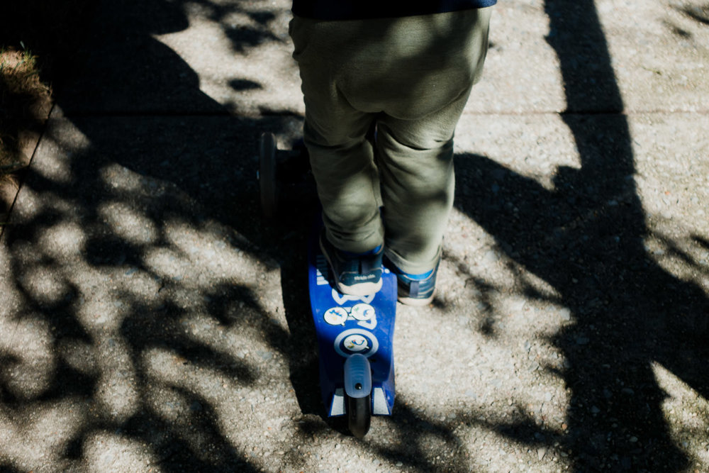 A little boy rides his scooter through shadows from the trees.