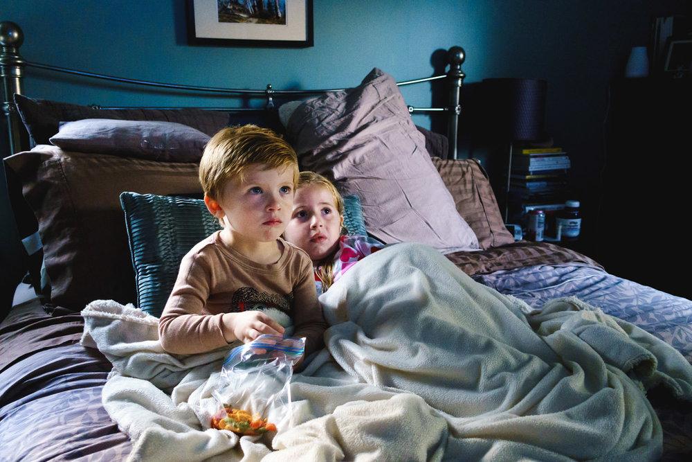Two siblings watch TV in bed.