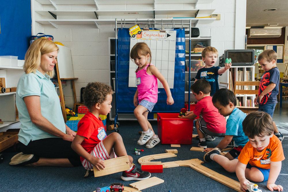 Preschoolers play in a room at school.