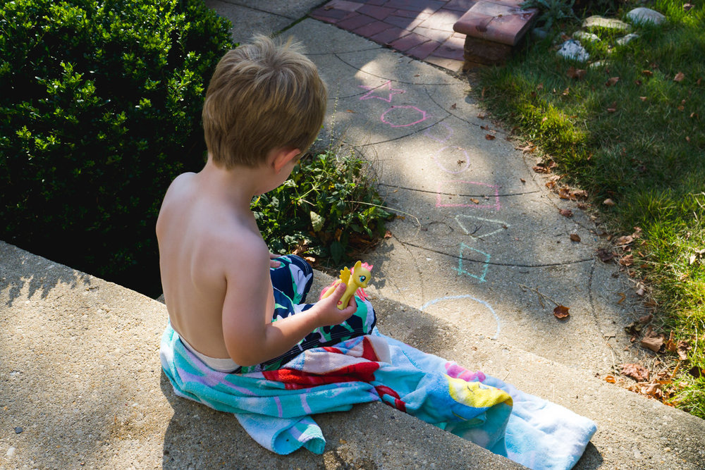 A small boy sits on a sunny porch wrapped in a towel.