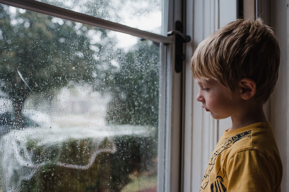 A little boy watches the rain through a glass storm door.