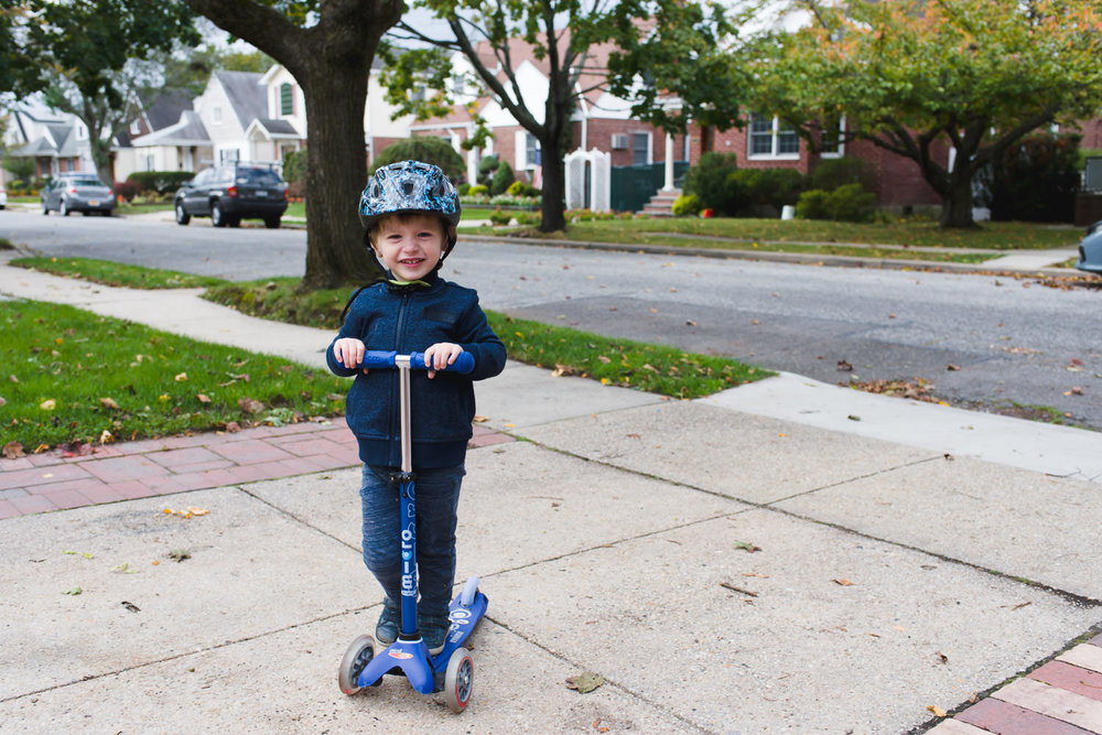 A little boy rides his scooter in a driveway.