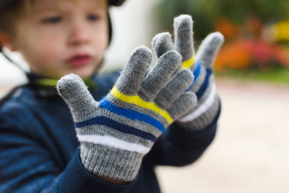 A little boy looks at his new gloves.