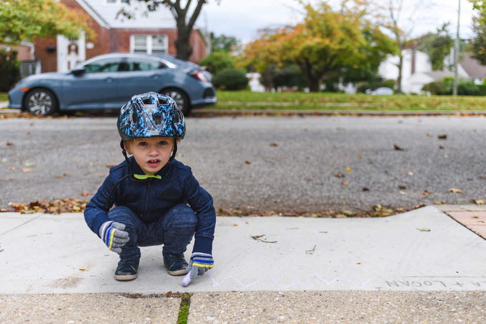 A little boy in a bike helmet draws on his driveway with chalk.