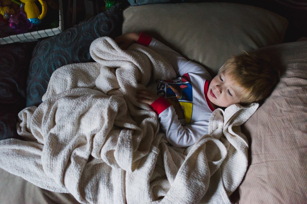 A little boy snuggles under a blanket.