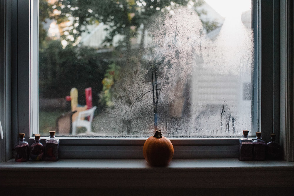 A small pumpkin sits on a window sill.