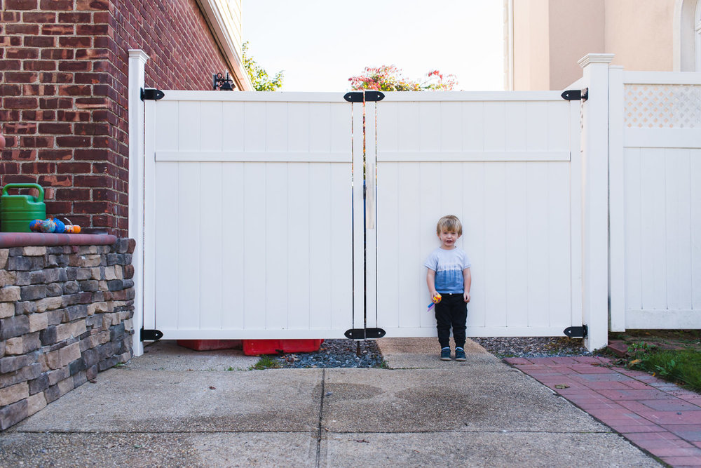 A little boy stands in front of a white fence.