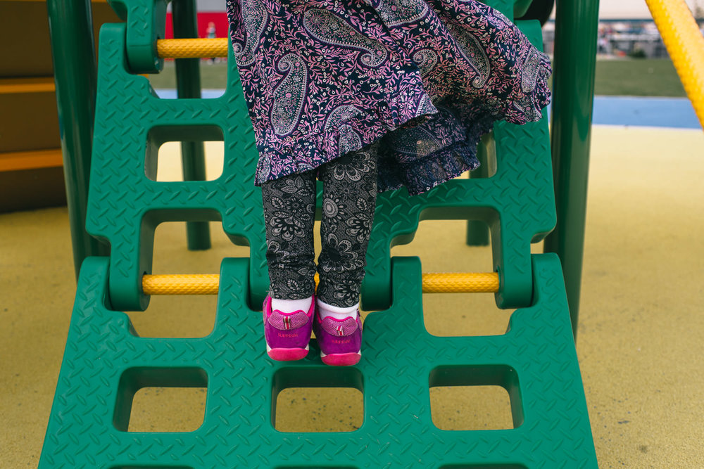 A girl climbs a play structure at Eisenhower Park.