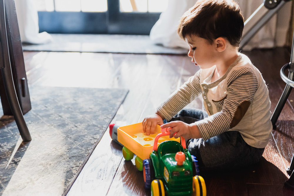 A little boy plays with a toy truck on the dining room floor.