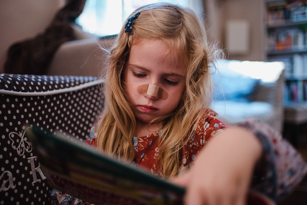 A little girl with a band-aid on her nose reads a book.