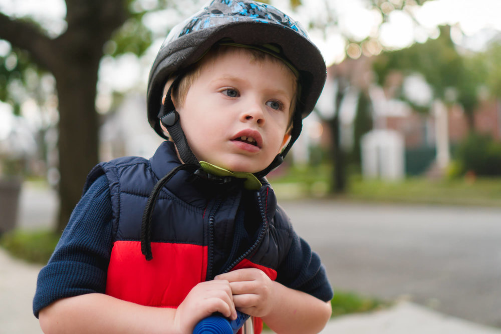 A little boy wears a scooter helmet.
