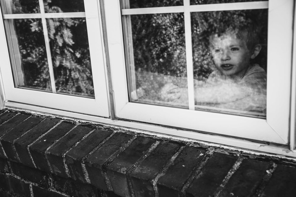 A little boy peeks out of his front window.