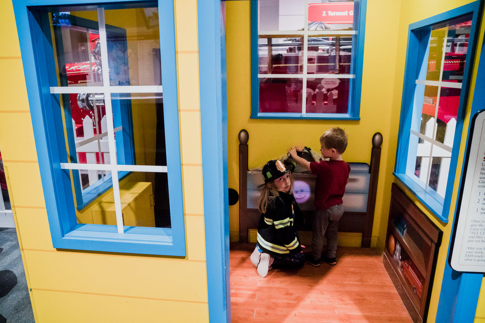 Two children play in a house at the Fire Museum.