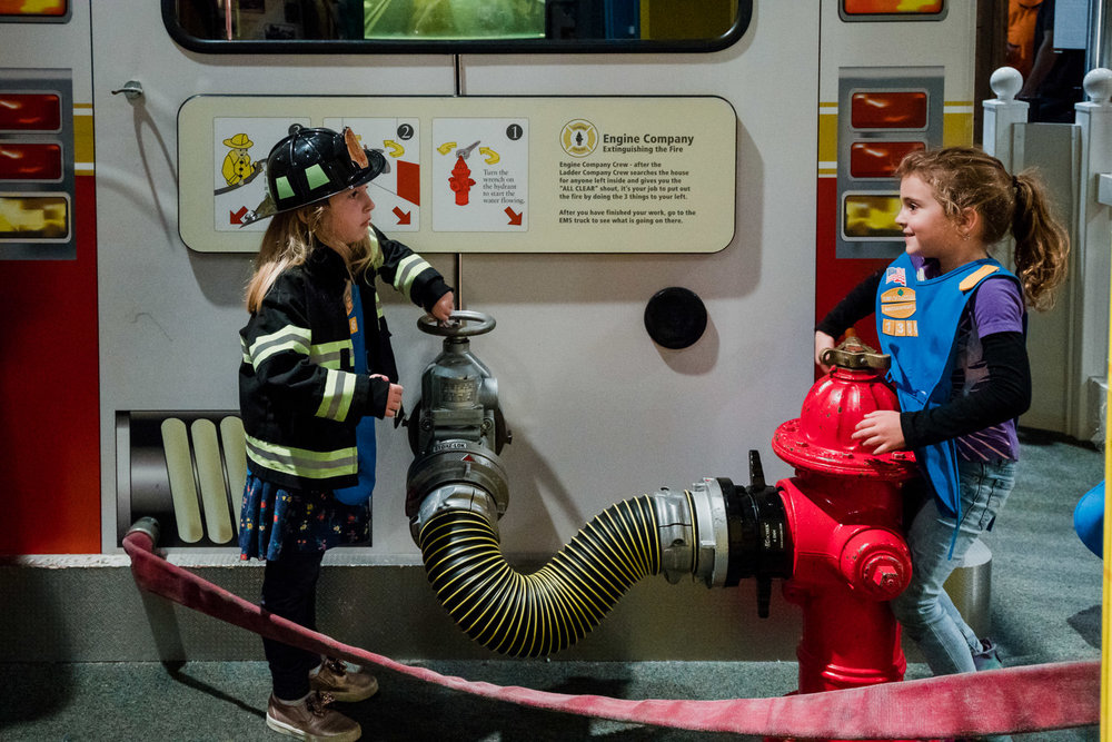 Two girls play at the Fire Museum.