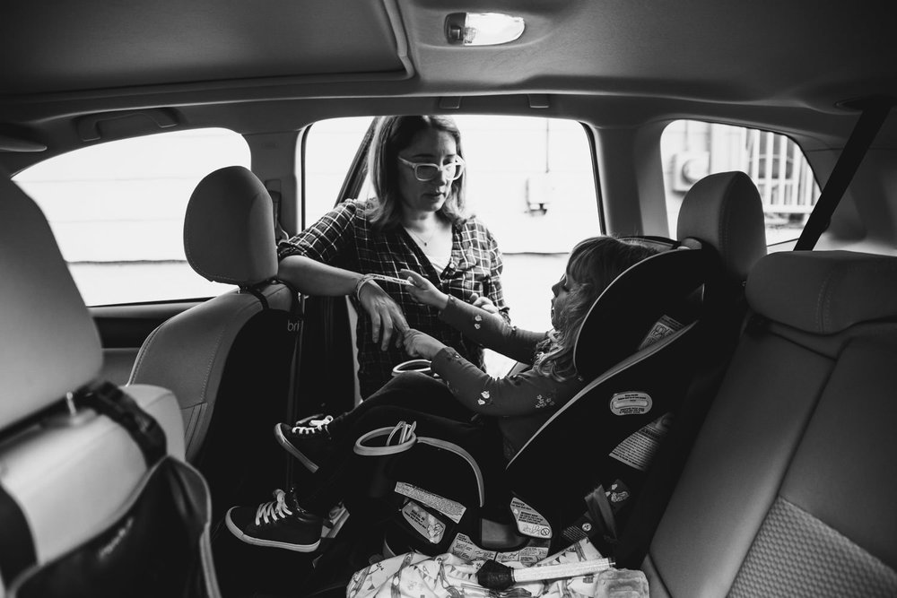 A mother fastens her daughter in her carseat.