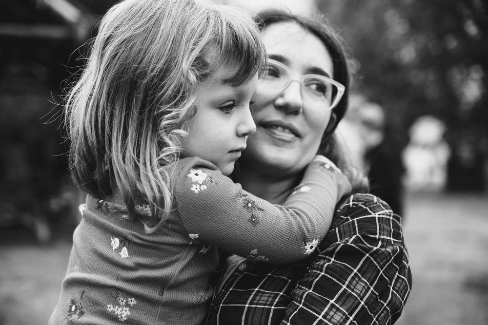 A mother holds her preschooler daughter.