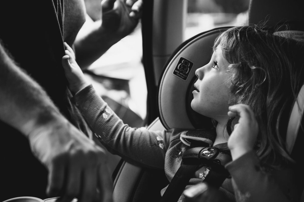 A little girl looks up at her father from her carseat.