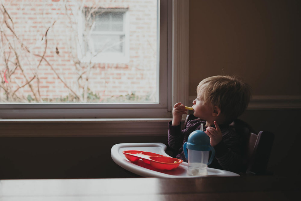 A little boy eats in his high chair and looks out a window.