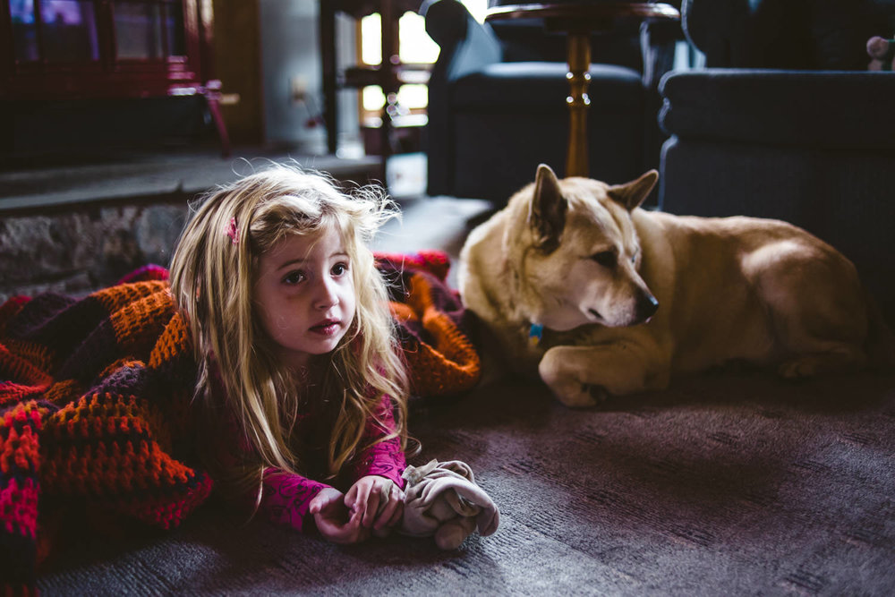 A little girl lies under a blanket with her dog.