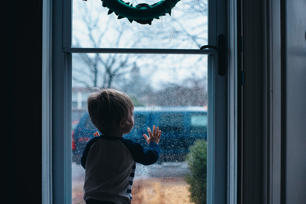 A little boy looks out his storm door in the winter.