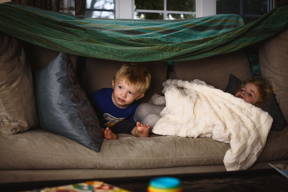 Children play in a couch fort.
