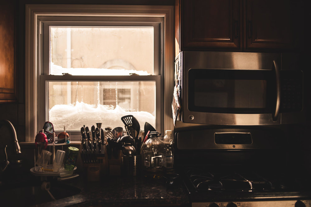 Snow piled up outside a kitchen window.