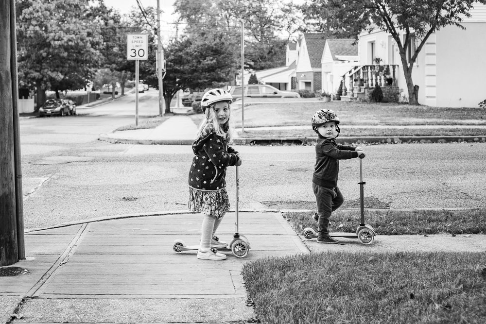 Two kids ride scooters down the sidewalk.