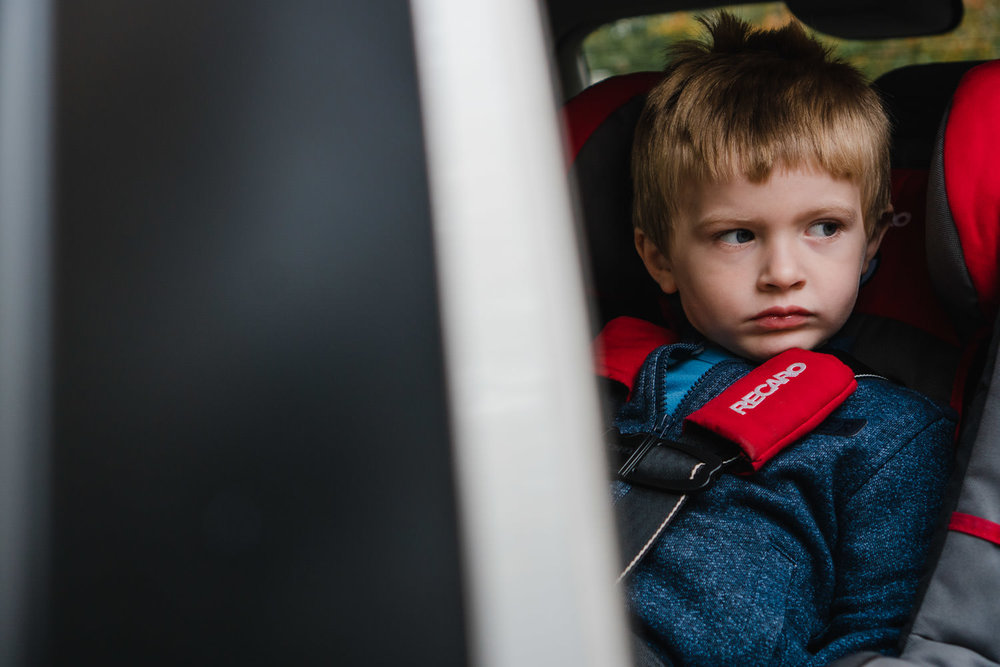 A little boy sits in his car seat.
