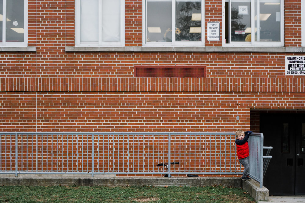 A little boy balances on a wall outside a school.