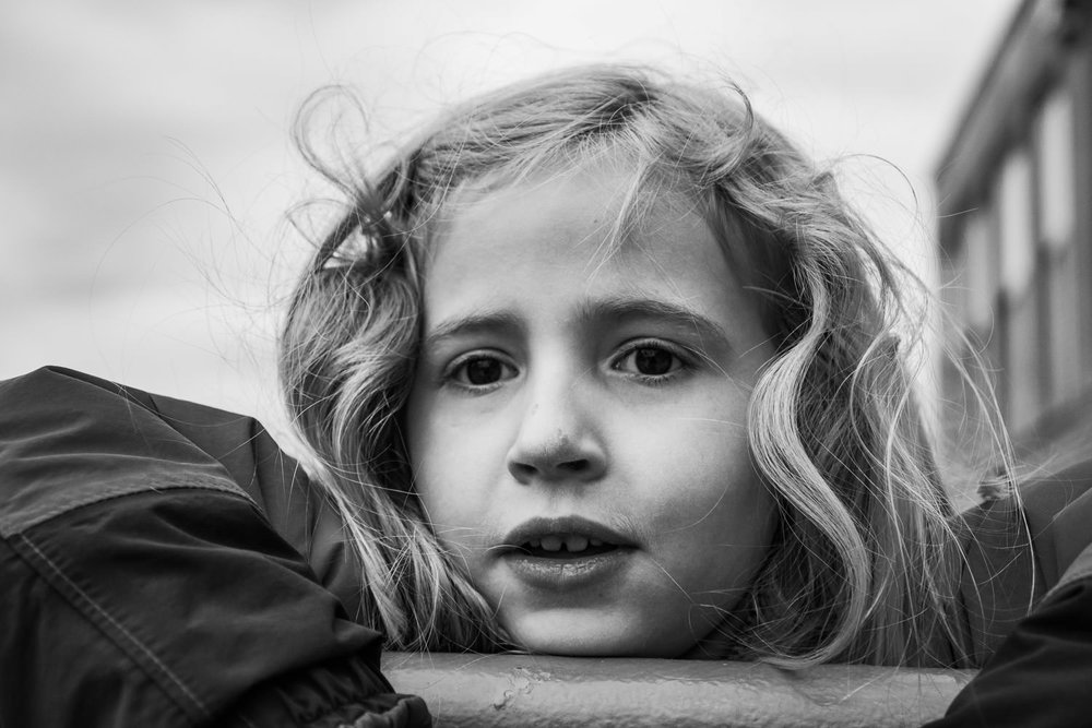 A portrait of a little girl outside her school.