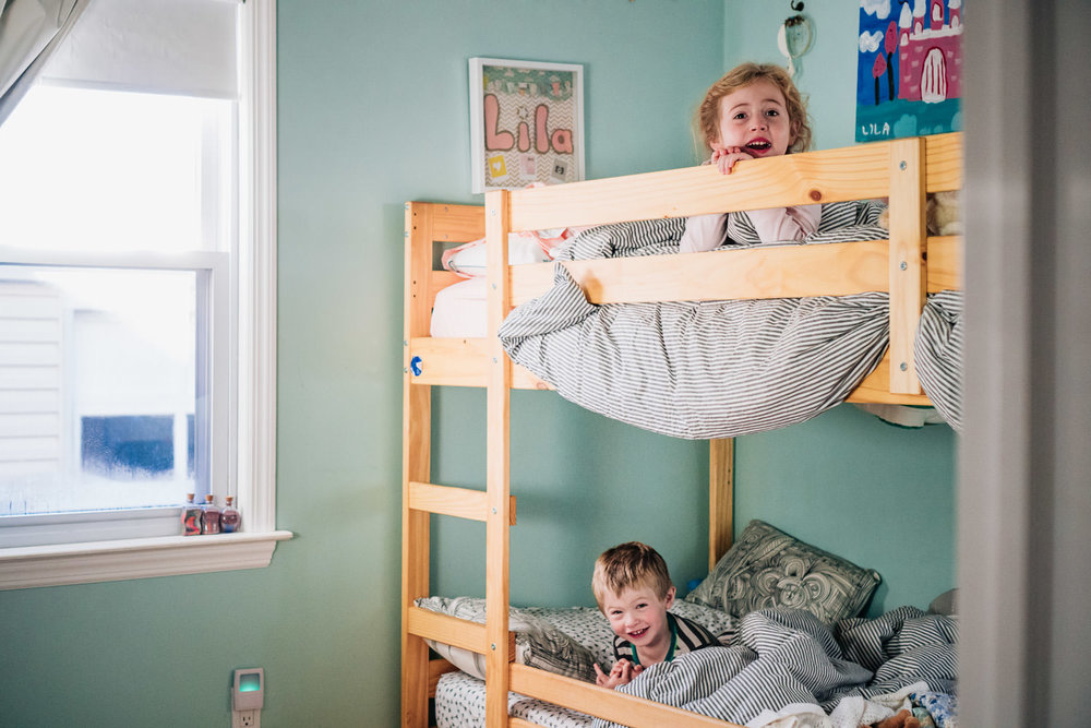 A brother and sister smile at the camera from their bunkbeds.