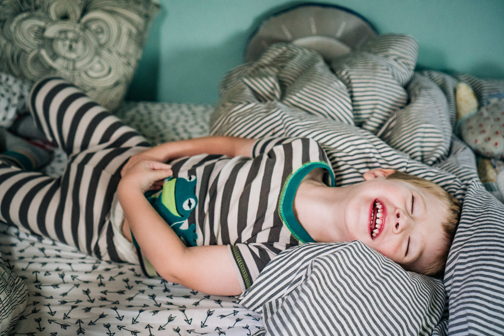 A toddler boy laughs in his bed.
