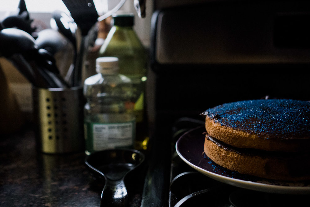 A cake in need of more frosting sits on a stovetop.