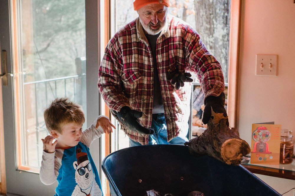 A man and his grandson gather firewood.