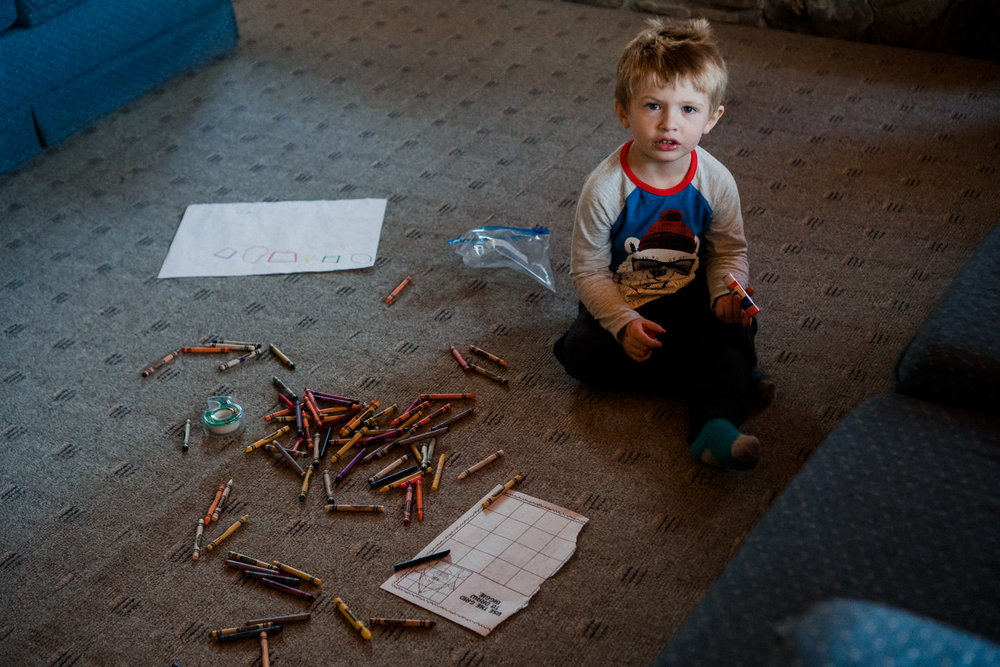 A little boy sits next to a pile of crayons.