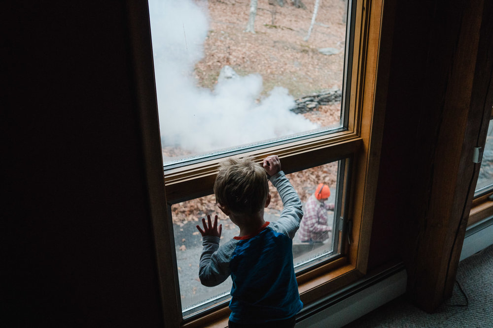 A little boy looks out a window at some smoke.