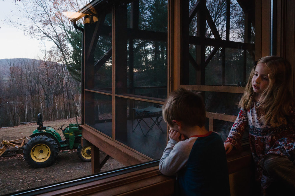 Two children look outside at the woods beyond.