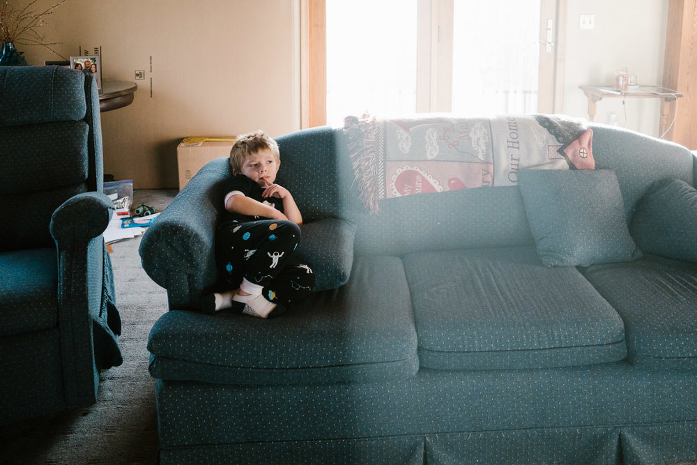 A little boy sits on a couch.
