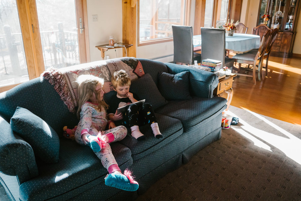 Children relax on a couch.