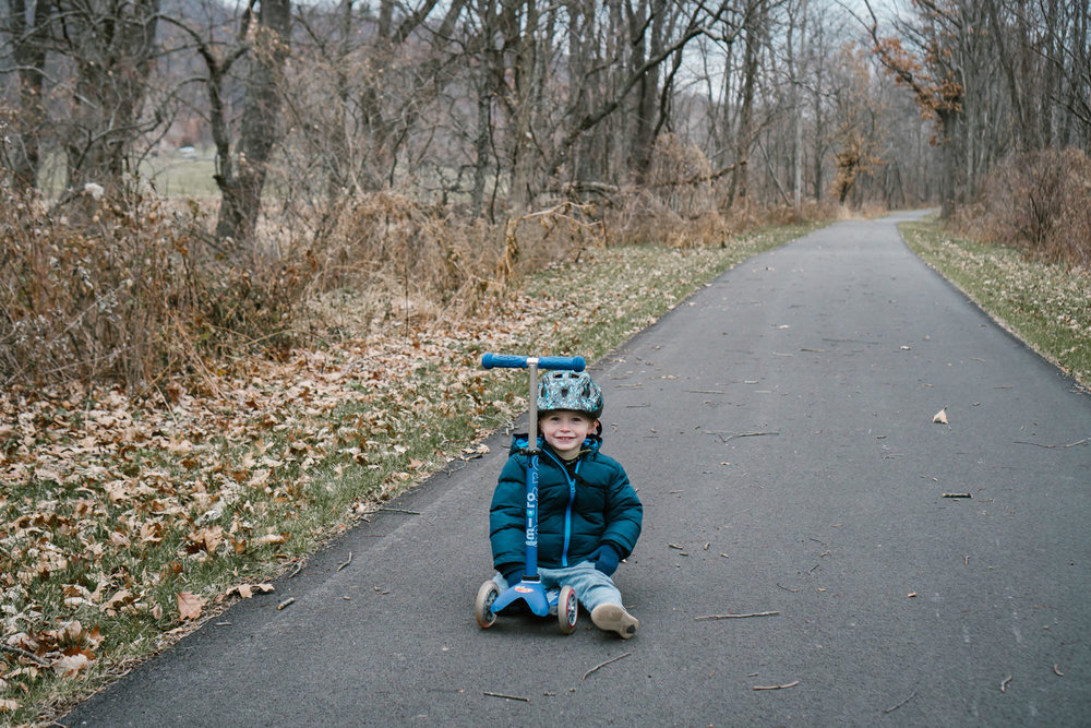 A little boy sits on a scooter in the middle of a trail.
