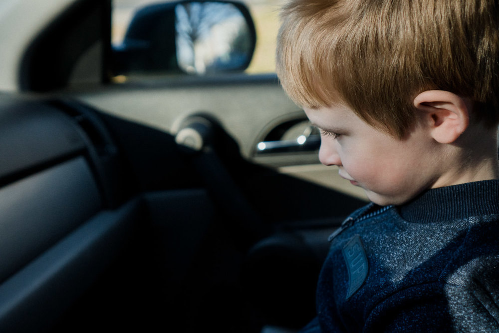A little boy sits in the front seat of a car.
