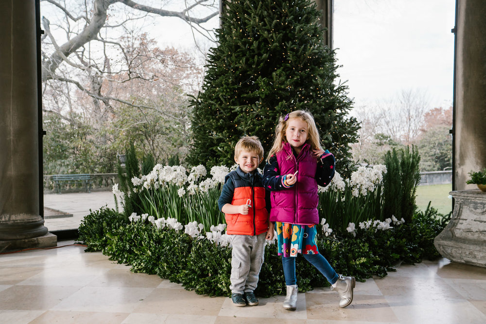Two children smile in front of the Christmas Tree at Old Westbury Gardens.