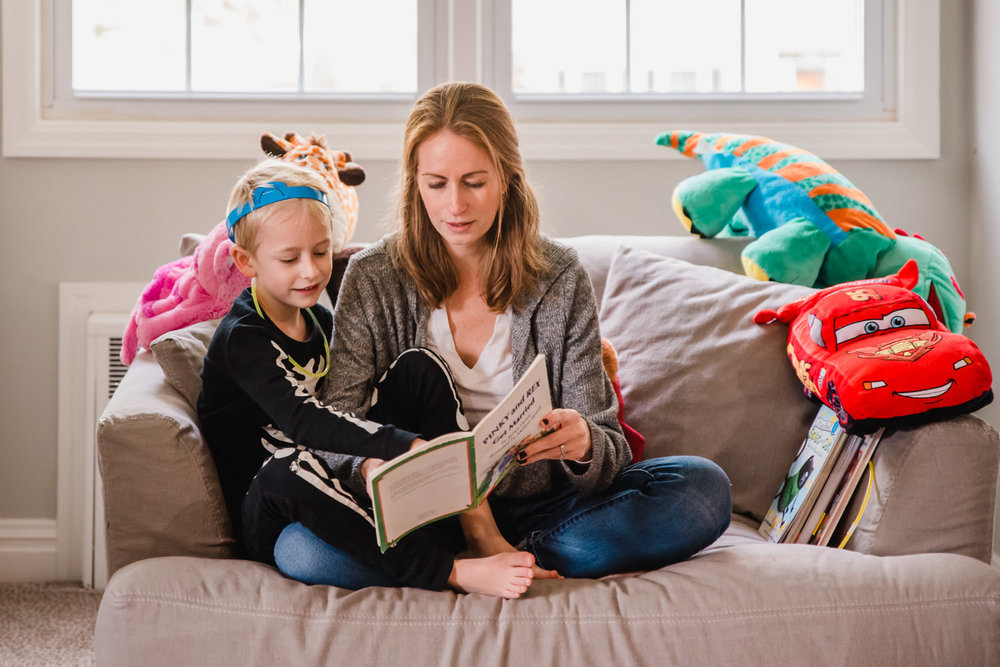 A mother reads a book to her son.