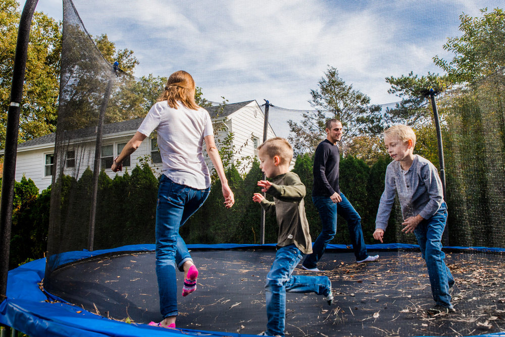 A family plays on their trampoline in the backyard.