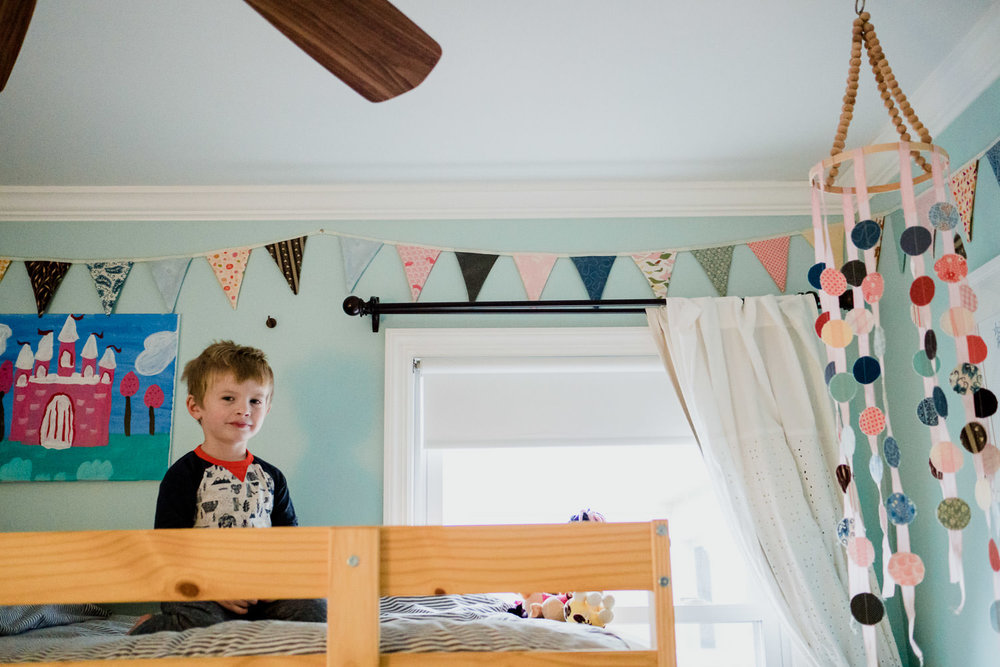 A little boy perches on the top bunk of a bunkbed.